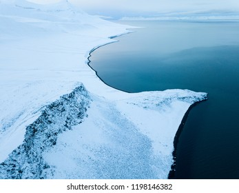 Winter drone views over a Svalbard coast lined by black beaches.