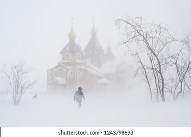 In winter, during a blizzard near the Cathedral of the Holy Trinity. People go through a snowstorm.
