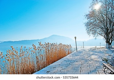 The winter embankment of Orestiada Lake with bright yellow reeds and misty mountains on the background, Kastoria, Greece.