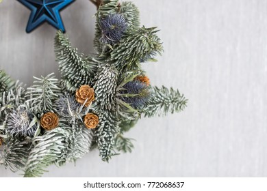 winter, environment, equipment concept. close up of conifer brunches weaved into one circle with buds of burdock, decorated with pinecones and blue star, covered with rime