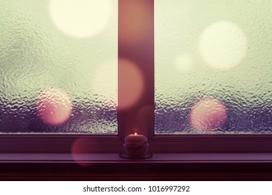 Winter evening. Frosted window, burning candle and purple bokeh lights.