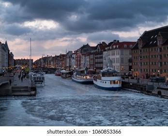 winter evening view of nyhavn copenhagen - with the harbor completely frozen