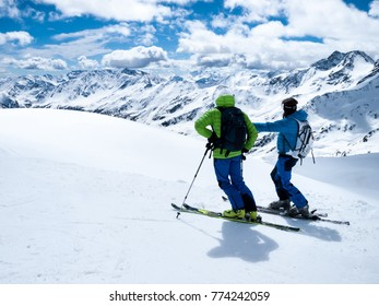 Winter extreme sport. A hiking trip on skis. Two skiers admire beautiful alpine landscapes.