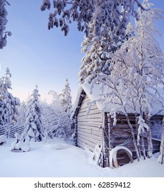 Winter fairy snow forest with pine trees and house at sunset. Finland