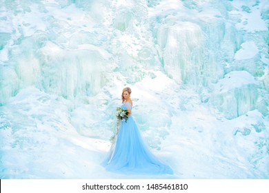 winter fairy tale on an ice waterfall a beautiful girl with long blonde hair and a blue dress with a long train holds a bouquet in her hand...
