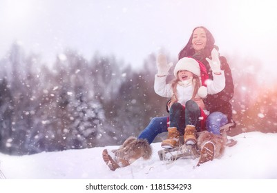 Winter fairy tale, a young girls ride a sled in the forest.