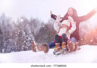 Winter fairy tale, a young mother and her daughter ride a sled in the forest. A girl on a sled with gifts on the eve of the new year in the park. Two sisters walk in a New Year's park and ride a sled