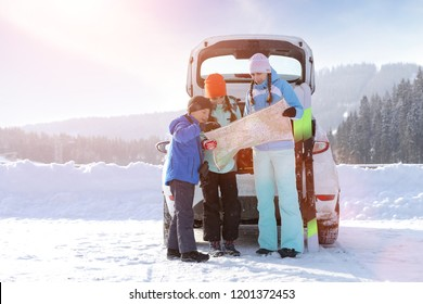 Winter family traveling navigate concept image. Young woman with her children trying to find the road with map