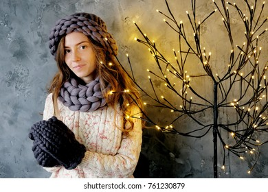 Winter fashion accessories.Young woman dressed for cold weather in grey snood, hat and mittens.