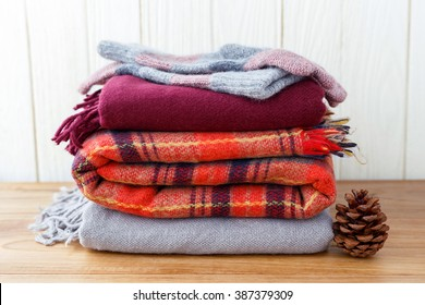 Winter fashion clothing with scarf gloves and blanket with wood background