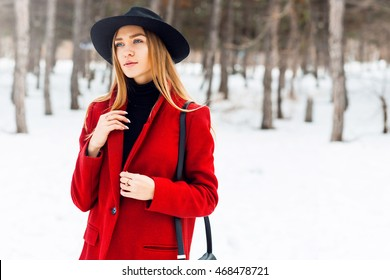 Winter fashion portrait of blonde student  woman in hat and red coat walking in  snow park with bag. Cold season.