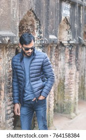 Winter fashion shoot of a handsome and good looking indian or arab looking male model with dark hair, black sunglasses and a navy blue softshell jacket in front of an old building