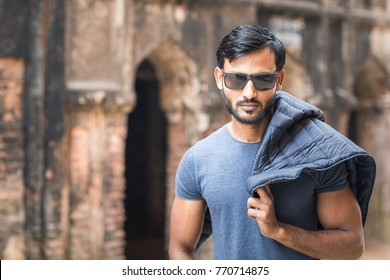 Winter fashion shoot with handsome and good looking indian or arab male fitness model with dark hair, black sunglasses and a beard, who is showing the winter collection with a chunky heavy knit shawl