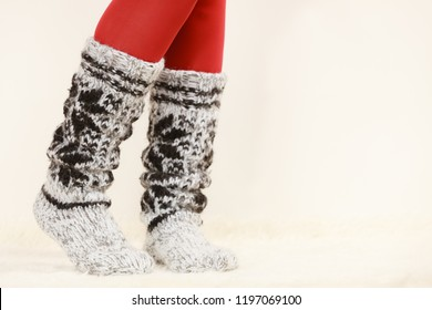 Winter fashion. Woman legs wearing fashionable wintertime clothes woolen warm socks and red tights