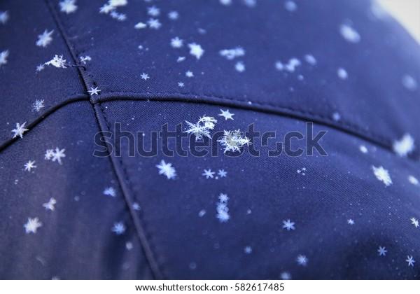 Winter in Finish Lapland. Snow crystals in form of hexagonal stars on a jacket.