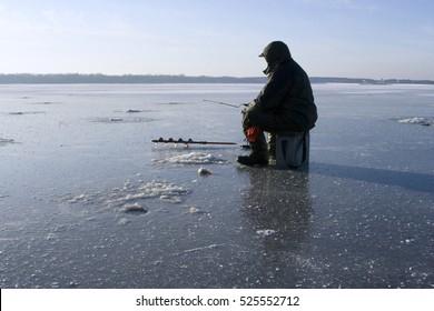 Winter fishing on lake. Ice drill and ice fishing rod on frozen lake.