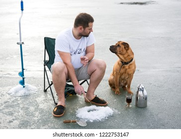 Winter fishing. Shar Pei is sitting with his owner on the ice on the lake.