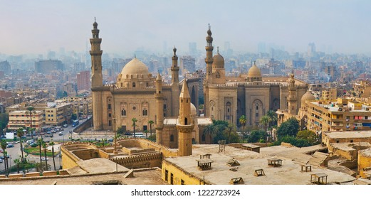Winter fog covers the old city, hides its slums and winding streets, only giant medieval mosques of Al Rifai' and Sultan Hassan with tall minarets are seen clearly from Saladin Citadel, Cairo, Egypt.