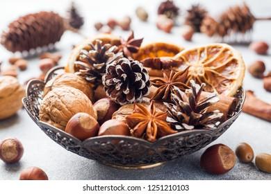 Winter food ingredients nuts cones oranges cinnamon star anise in a bowl. Rustic style