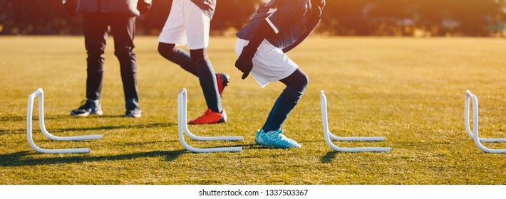 Winter Football Soccer Training Session with Hurdles. Athlete Player Practice Hurdle Jump