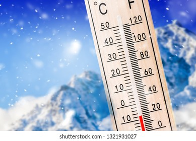 Winter forecast indicator mountines background with sun, Thermometer in snow. Temperature shows minus degree celsius.