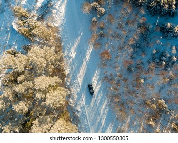 Winter forest with road and car from top flying