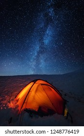 Winter frost night in the high mountains of the Ukrainian Carpathians, with overnight stay in a red tent under the glow of the Milky Way