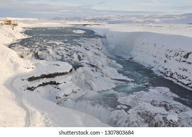 Winter at the frozen Gullfoss waterfall taking glacial water over a deep crevice in Iceland.