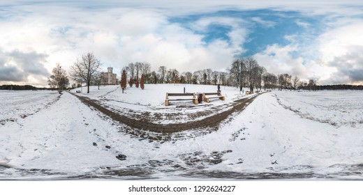 Winter full spherical seamless panorama 360 degrees angle view on road in a snowy park with blue sky near frozen city lake in equirectangular projection. VR AR content