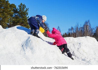 Winter fun children. Brother helps sister to climb to the top of a snowy mountain