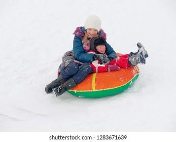 Winter fun. children ride from a snow hill.