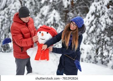 winter fun. a girl and a man making snowballs