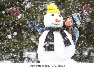 Winter fun, winter leisure and winter vacation - young woman having fun making snowman with falling snow