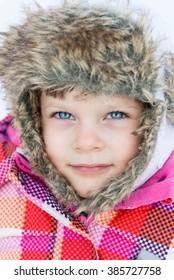Winter fun - Portrait of Happy child girl on a winter walk in nature