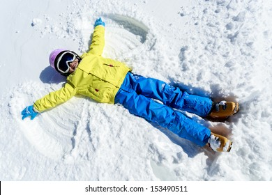 Winter fun - Snow Angel - young skier  girl playing in snow