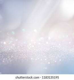 Winter gentle sparkle snowy blurry background in light blue pink tones. Christmas backdrop defocused with beautiful light, abstract shiny snowflakes flake of snow in blur, copy space.
