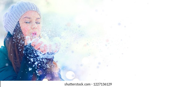 Winter girl blowing snow. Beauty Joyful Model Girl having fun in winter park. Beautiful young woman laughing outdoors. Enjoying nature. Wide angle Border design, isolated on white background