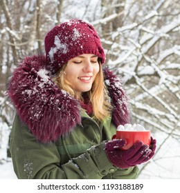 Winter girl with a cup of tea, cold and snow, winter holidays