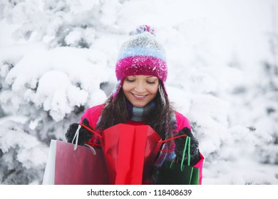 winter girl with gift bags on snow background