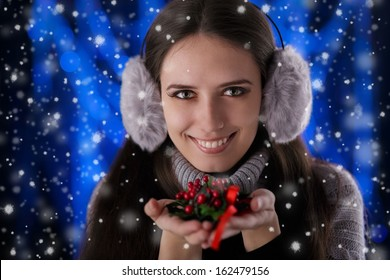 Winter Girl Holding a Christmas Decoration - Beautiful girl holding a Christmas decoration with snow falling around her.