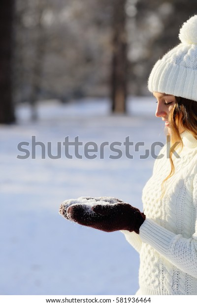 Winter girl holding snow in hands