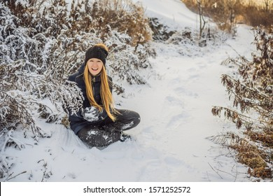 winter girl throwing snowball at camera smiling happy having fun outdoors on snowing winter day playing in snow. Cute playful young woman outdoor enjoying first snow