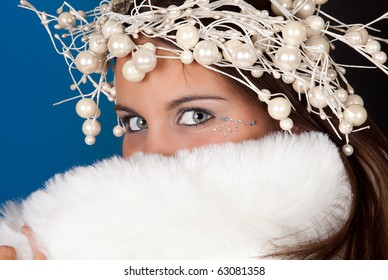 Winter girl wearing a white fur coat and pearl christmas wreath
