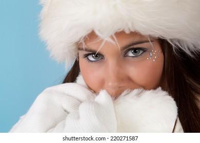 Winter girl with white fur hat wearing warm fur hat