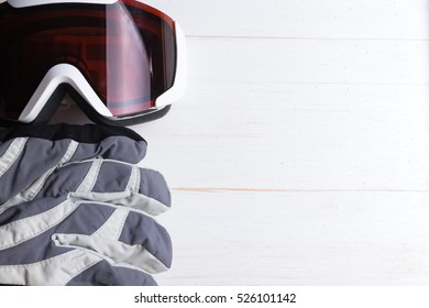 Winter gloves and goggles on white natural wooden table background. Concept of skiing or snowboarding. Copy space on the right. Flat lay top view.