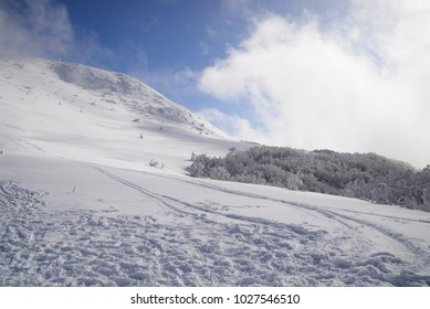 winter going over the high mountain and skies and snowboard paths covered by snow - landscape