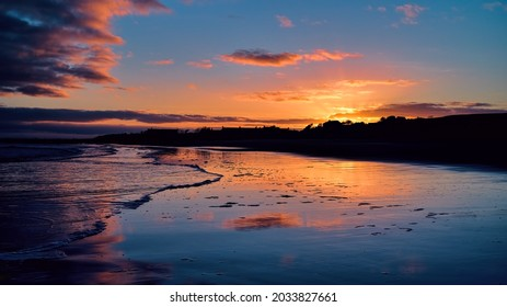 Winter golden sunset on Brora beach in the Highlands with reflections in the wet sand