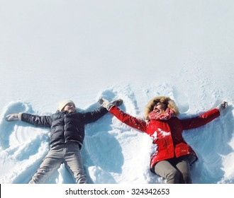 Winter happy family mother and son child lying on snow playing having fun together at sunny day, empty copy space