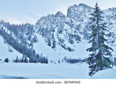 Winter at Heather Lake in North Cascade Mountains of Washington state with snow covered mountains & a lone evergreen tree. The five mile round trip trail to the lake is near the city of Granite Falls.
