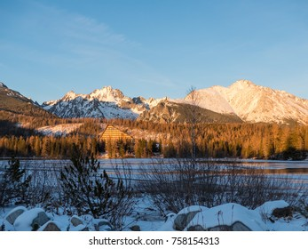 Winter in High Tatras. Winter view of frozen surface of Strbske Pleso (Tarn) with hotel and peaks of High Tatra mountains in background. Winter lake, mountains and blue sky.